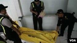 Polisi membawa jenazah korban kebakaran ferry ke rumah sakit di Surabaya, Jawa Timur (28/9).