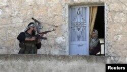 Un miembro del ejército libre de Siria habla con una mujer durante una patrulla en busca de fuerzas gubernamentales en Haram, Idlib, Siria.