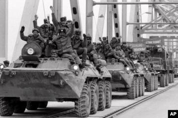 Hình minh họa - Máy bay trực thăng của Hoa Kỳ rời đi, trong khi chiến binh Taliban ngồi trên chiếc xe tăng bị bỏ hoang, bao quanh bởi những bông hoa anh túc đỏ.