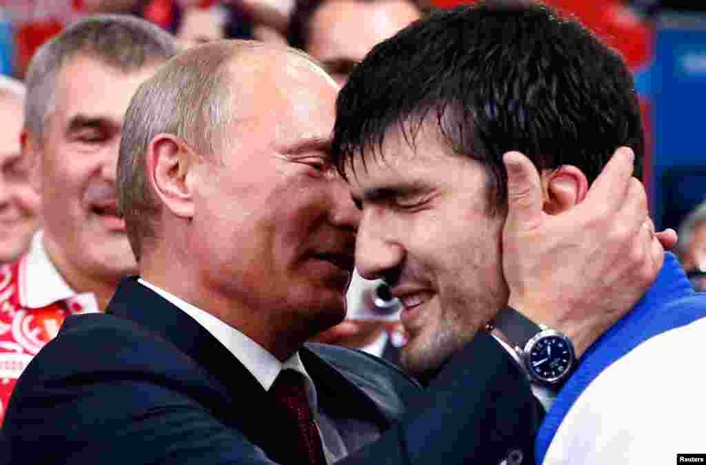 Russian President Vladimir Putin congratulates Russia's Tagir Khaibulaev after he defeated Mongolia's Tuvshinbayar Naidan in their men's -100kg final judo match.