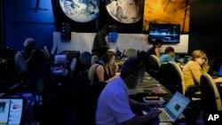 ບັນດານັກຂ່າວກຳລັງປະຕິບັດງານ ຢູ່ສູນກາງຂ່າວ ຕຽມລາຍງານ ກ່ຽວກັບຍານ Juno ຂອງອົງການ NASA ທີ່ໂຄຈອນອ້ອມດາວພະຫັດ.