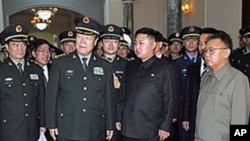 北韓領導人金正日和他的兒子金正恩(中)在平壤接待中國軍事代表團(資料照片)