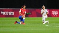 Sapporo'daki olimpiyat maçında protesto amacıyla diz çöken Şili ve Kanada kadın milli takımlarının oyuncuları.