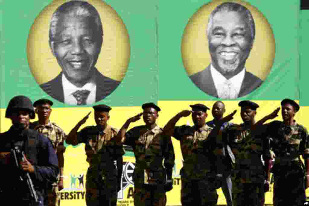 Members of the Umkhonto We Sizwe Military Veterans Association (MKMVA) salute in front of posters of former presidents of the African National Congress (ANC), Nelson Mandela (L) and Thabo Mbeki, during the ANC's centenary celebration in Bloemfontein Janua