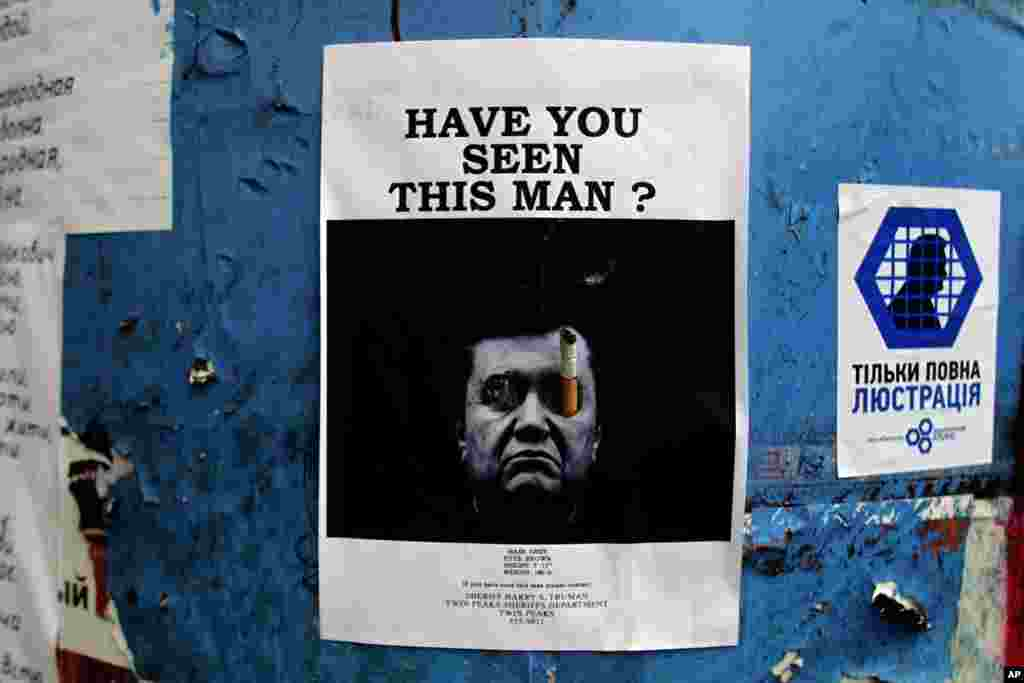 A poster with a photo of ousted Ukrainian President Viktor Yanukovych, who fled the Kyiv, is seen posted on a barricade in central Kyiv, Feb. 27, 2014.