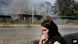 Một phụ nữ ngồi khóc trước căn nhà đang cháy sau các vụ pháo kích ở Donetsk, miền đông Ukraine, ngày 7/9/2014.