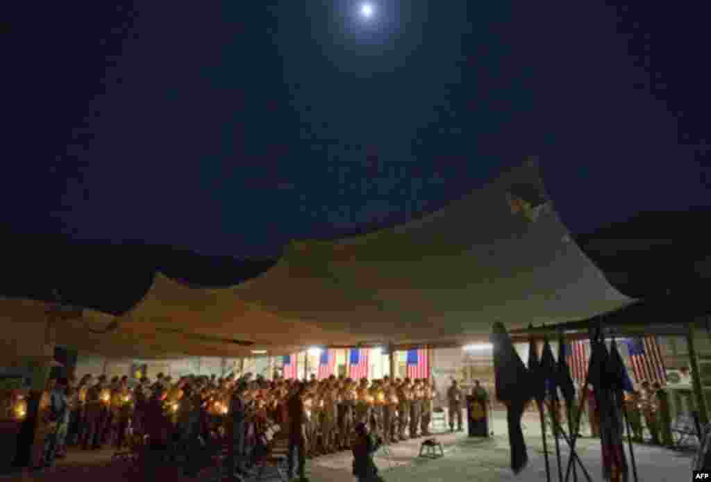 Soldiers with the U.S. Army's 25th Infantry Division, 3rd Brigade Combat Team, 2nd Battalion 27th Infantry Regiment based in Schofield Barracks, Hawaii, hold a ceremony under a full moon to commemorate the tenth anniversary of the 9/11 attacks and soldier