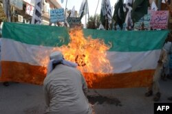 FILE - Pakistani activists of the Islamic organization Jamaat-ud-Dawa torch an Indian flag during a demonstration in Quetta, Oct. 10, 2014.
