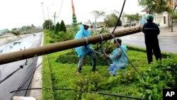 Công nhân điện lực đang sửa chữa cột điện đổ ở tỉnh Phú Yên, miền trung Việt Nam, hôm 4/11, sau khi Damrey tràn qua.