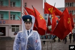 FILE - A North Korean traffic police woman directs vehicles at a street junction while behind her the sidewalk is decorated with flags of the ruling party, the Workers' Party on May 5, 2016, in Pyongyang, North Korea.