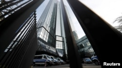 FILE - Police vehicles are parked in front of Deutsche Bank headquarters as roughly 170 criminal police officers, prosecutors and tax inspectors searched Deutsche Bank offices in and around Frankfurt, Germany, Nov. 29, 2018, on money laundering allegations.