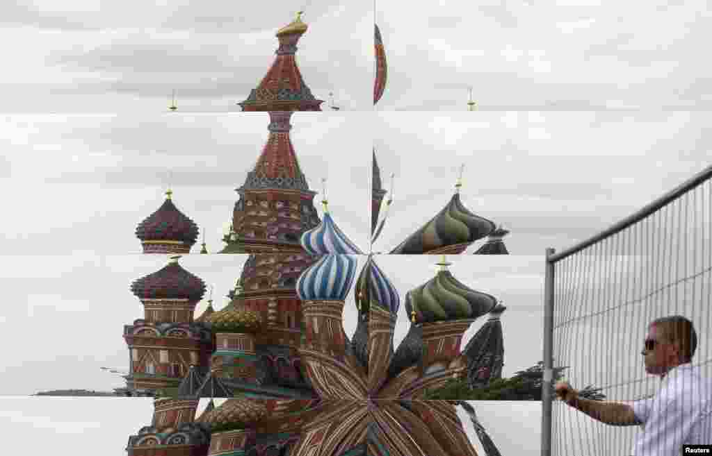 A reflection of St. Basil's Cathedral is seen as a security guard opens a gate near a mirrored pavilion being built on Red Square in Moscow.