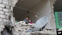 Сирійські діти у частково знищеному будинку