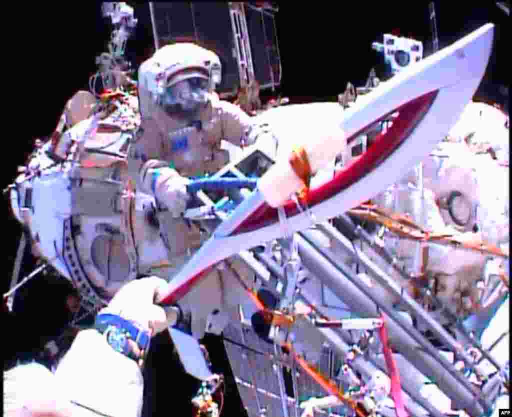 In this image obtained from NASA TV, Cosmonauts Oleg Kotov and Sergei Ryazansky (rear) perform a handoff of the Sochi 2014 Winter Olympic Games Torch during a spacewalk outside the International Space Station, Nov. 9, 2013.