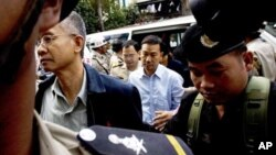 Thai activists Veera Somkwamkid, second left, a core leader of Yellow Shirts and Panich Vikitsreth, a member of Parliment of the ruling Democrat party, second right, are escorted by Cambodian court security personnel at Phnom Penh Municipal Court, file photo.