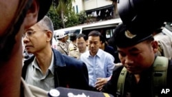 Thai activists Veera Somkwamkid, second left, a core leader of Yellow Shirts and Panich Vikitsreth, a member of Parliment of the ruling Democrat party, second right, are escorted by Cambodian court security personnel at Phnom Penh Municipal Court, last Th