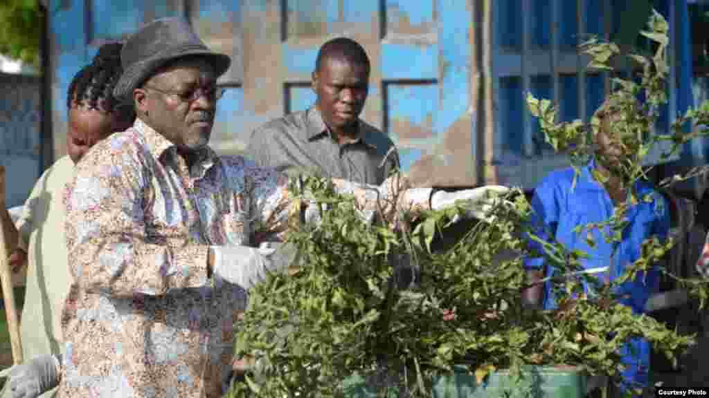 Le président tanzanien John Magufuli met des ordures dans une poubelle lors de travaux collectifs de nettoyage en commémoration du 54e anniversaire de l'indépendance du Tanganyika.