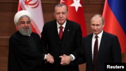 FILE - Presidents Hassan Rouhani of Iran, Recep Tayyip Erdogan of Turkey and Vladimir Putin of Russia hold a joint news conference after their meeting in Ankara, Turkey, April 4, 2018.