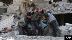 Syrians rescue a child following a reported government airstrike in the rebel-held town of Hamouria, in the besieged Eastern Ghouta region on the outskirts of the capital Damascus, Feb. 21, 2018.