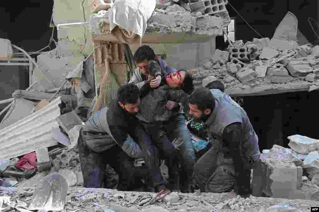 Warga Suriah menyelamatkan seorang anak yang terluka akibat serangan udara pasukan Suriah di Hamouria, Ghouta timur, di luar ibu kota Damaskus.