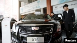 Customer Wang Pan looks around Cadillac's XTS model at its dealership in Beijing, China, March 14, 2016.