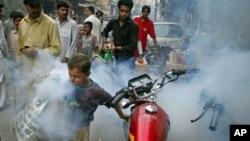 ເດັກຊາຍຜູ້ນຶ່ງກໍາລັງແລ່ນໄປກ່ອນ ຊາຍຜູ້ນຶ່ງທີ່ກໍາລັງສີດ ຢາຂ້າຍຸງ ຢູ່ຕາມຖະໜົນສາຍຕ່າງໆ ຂອງເມືອງ Lahore, ປະເທດປາກິສຖານ ເພື່ອຕ້ານກັບການແຜ່ລະບາດຂອງໄຂ້ເລືອດອອກ ໃນວັນທີ 20 ກັນຍາ, 2011.