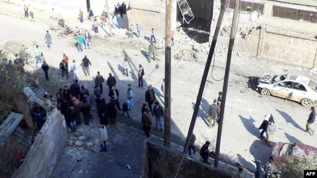 A handout picture released by the Syrian Arab News Agency shows Syrians inspecting the site of a car bomb blast in the northwestern city of Idlib, January 16, 2013.
