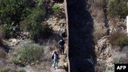 Пограничная стена, разделяющая США и Мексику. С левой (мексиканской) стороны видны люди, которые выбирают место для нелегального пересечения границы. Архивное фото.