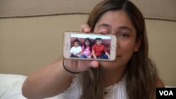 FILE - Yeni Gonzalez shows a photo of her children.