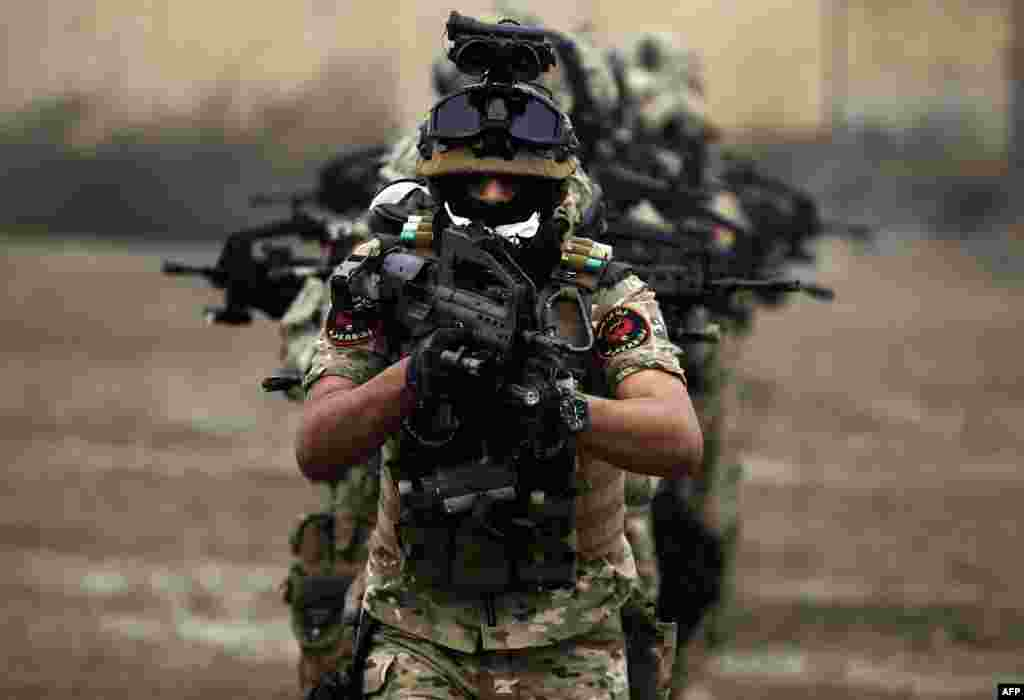 "Members of Iraq's Rapid Response military unit take part in a ""counter-terrorism"" training at a military base inside Baghdad International Airport. The exercises are being held over a period of four months in cooperation with the Italian forces in Iraq."