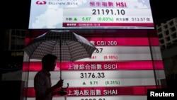 Seorang pria melintasi panel yang menunjukkan anger indeks saham China dan Indeks Hang Seng di Hong Kong, China (2/9).