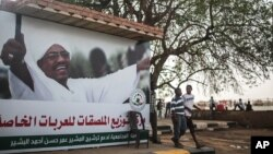 "Sudanese boys walk past an election campaign banner in support of President Omar al-Bashir that reads ""community commission in support of nominating Marshal Omar al-Bashir, in Khartoum, Sudan, April 11, 2015."
