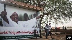 Dua orang anak laki-laki melewati poster kampanye Presiden Sudan, Omar al-Bashir, di Khartoum, Sudan (11/4). (AP/Mosa'ab Elshamy)