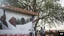 2015年4月15日苏丹男孩从支持现总统巴希尔的海报前走过。
