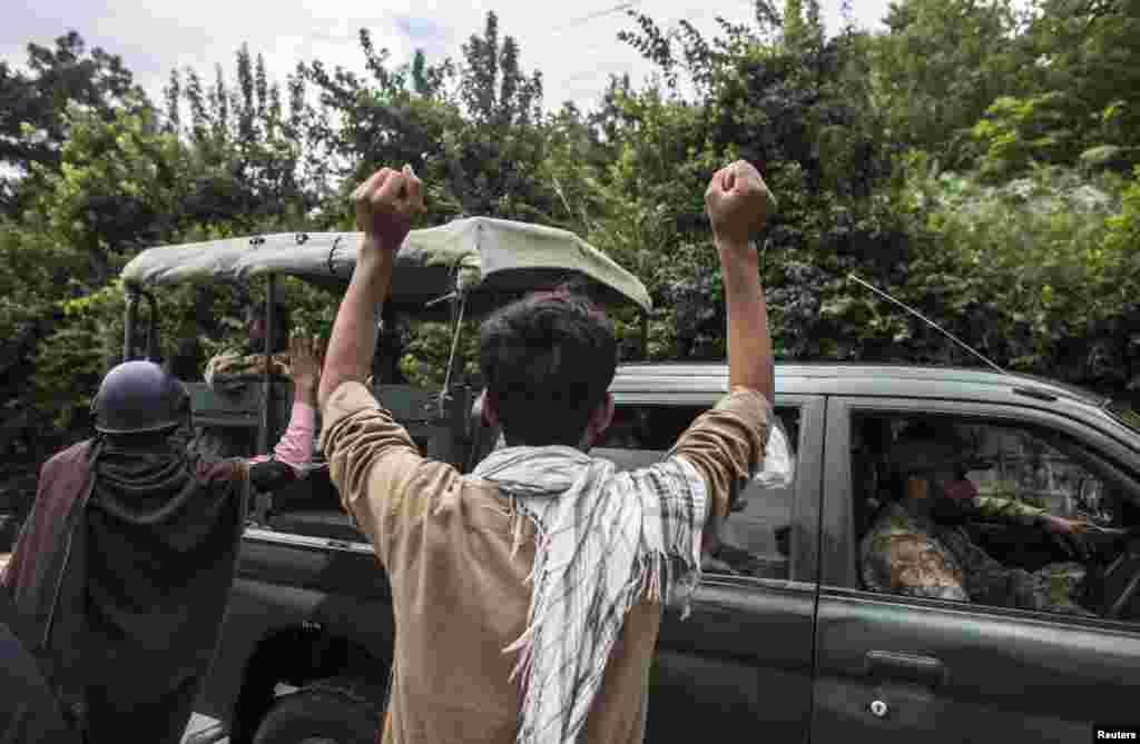 فوج کی ایک گاڑی مظاہرین کے قریب سے گزر رہی ہے۔