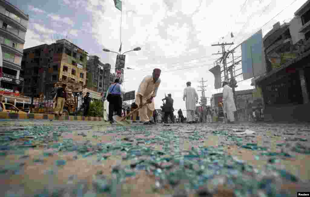 Rescue workers collect shattered glass from the site of the bomb blast on University Road in Peshawar, April 29, 2013.