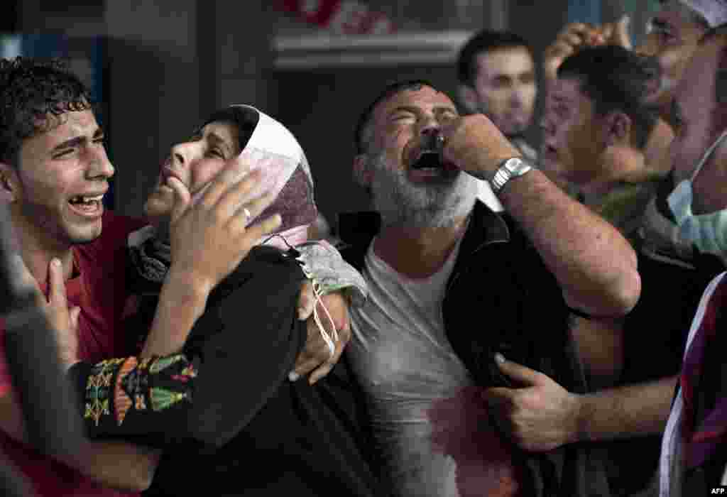 Palestinian mourners cry at Gaza City's al-Shifa hospital after an explosion killed at least seven children in a public playground in the beachfront Shati refugee camp. Palestinian medical sources blamed the killings on air strikes launched by the Israeli military, which in turn said Hamas had misfired its own rockets at the camp and at the Shifa hospital.
