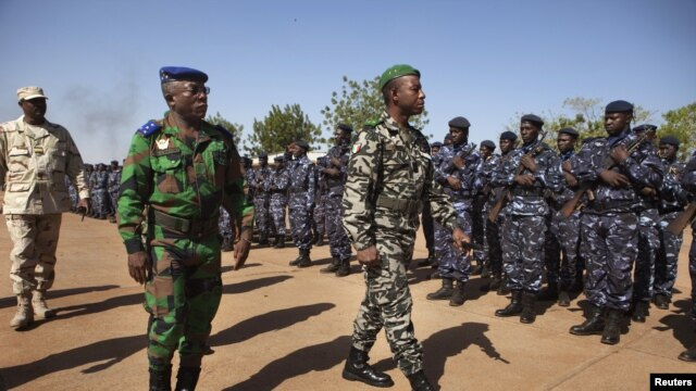 Ivory Coast army chief-of-staff Soumaila Bakayoko (L) and Malian army chief-of-staff Ibrahima Dahirou Dembele (C) inspect Malian troops at an air base in Bamako, January 16, 2013.