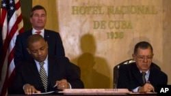 U.S.Transportation Secretary Anthony Foxx and Cuba's Minister of Transportation Adel Yzquierdo Rodriguez, right, sign the airline transportation agreement as Assistant Secretary of State for Economic and Business Affairs Charles Rivkin, top left, looks on