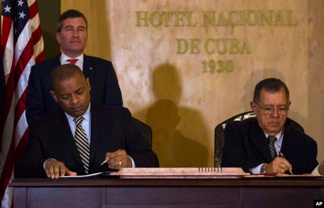 U.S.Transportation Secretary Anthony Foxx and Cuba's Minister of Transportation Adel Yzquierdo Rodriguez, right, sign the airline transportation agreement as Assistant Secretary of State for Economic and Business Affairs Charles Rivkin, top left, looks on in Havana, Cuba, Feb. 16, 2016.