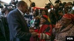 Rais wa Kenya Uhuru Kenyatta akisalimiana na mpiga kura mkongwe muda mfupi kabla ya kupiga kura katika eneo la Gatundu South, Kaunti ya Kiambu siku ya Alhamisi.