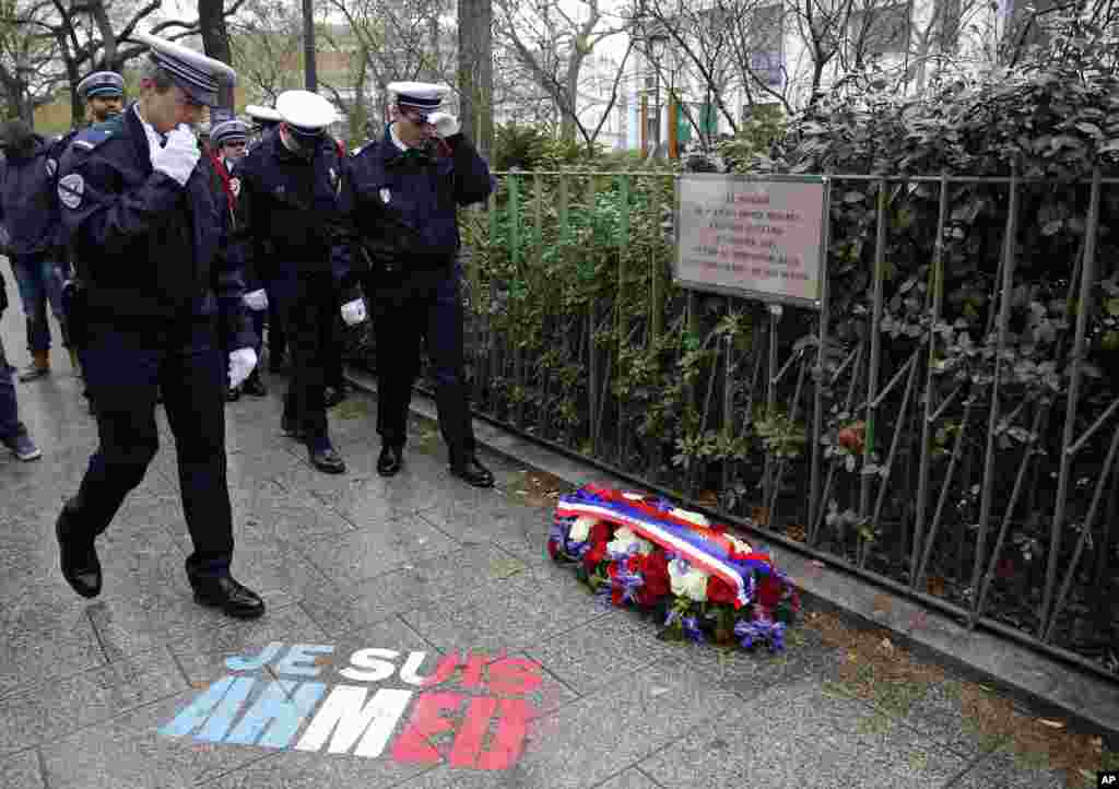 "Policemen walk past spray paint on the sidewalk reading: ""Je suis Ahmed,"" or ""I am Ahmed,"" in the red, white and blue of the French flag near a plaque commemorating late police officer Ahmed Merabet in Paris, Tuesday Jan. 5, 2016."