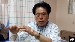 FILE - An off-duty helmsman Oh Yong-seok of the sunken ferry Sewol speaks on a bed at Mokpo Hankook Hospital where he gets treatment for minor injuries in Mokpo, South Korea, April 19, 2014