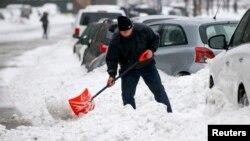 Un hombre palea para tratar de desatascar su vehículo que quedó atrapado por la nieve en Nueva York.