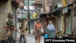 سری نگر میں فوجی گشت کر رہے ہیں جبکہ دو خواتین خریداری کیلئے جا رہی ہیں