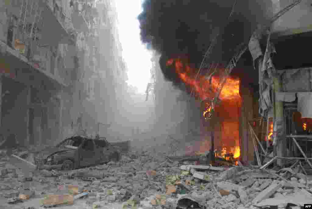 Debris cover a street and flames rise from a building following a reported air strike by Syrian government forces during the Friday prayer in the Sukkari neighborhood of the northern city of Aleppo.