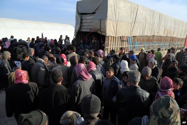 In this photo provided by Turkey's Islamic aid group of IHH, Syrians fleeing the conflicts in Azaz region, congregate at the Bab al-Salam border gate, Syria, Feb. 5, 2016.