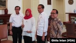 Baiq Nuril, disaksikan oleh Presiden Joko Widodo menerima salinan amnesti dari Menkumham Yasonna Laoly, di Istana Kepresidenan Bogor, Bogor, Jumat, 2 Agustus 2019. (Foto: VOA/Ghita)