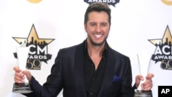 Luke Bryan poses in the press room with the awards for entertainer of the year and vocal event of the year at the 50th annual Academy of Country Music Awards, April 19, 2015, in Arlington, Texas.