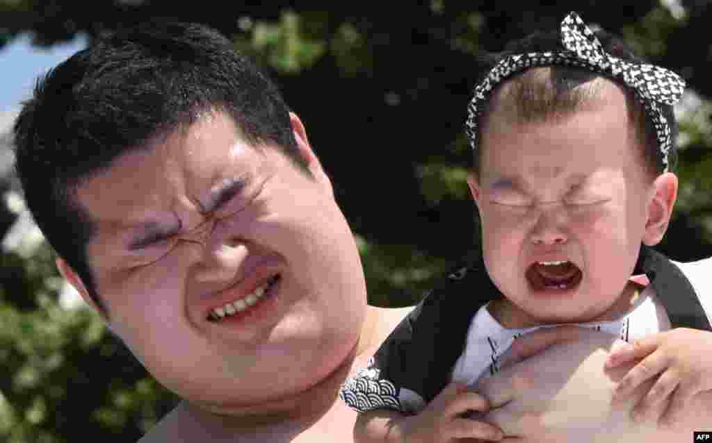 កូនសិស្សកីឡាចំបាប់ស៊ូម៉ូ បីក្មេងម្នាក់ដែលកំពុងយំក្នុងការប្រកួត « ទារកស៊ូម៉ូយំ (Baby-cry Sumo)» នៅក្នុងព្រះវិហារ Sensoji ក្នុងទីក្រុងតូក្យូ ប្រទេសជប៉ុន កាលពីថ្ងៃទី៣០ ខែឧសភា ឆ្នាំ២០១៥។